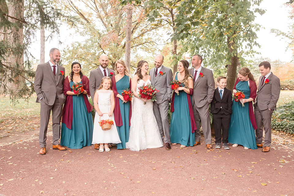 groom and groomsmen in brown suits with red ties and brown shoes with the bride in an ivory lace gown with her bridesmaids in teal colored gowns with red shawls