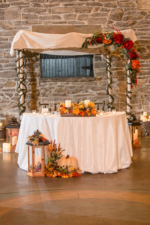 indoor décor with fall vibes with colorful leaves and pumpkins at sweetheart table