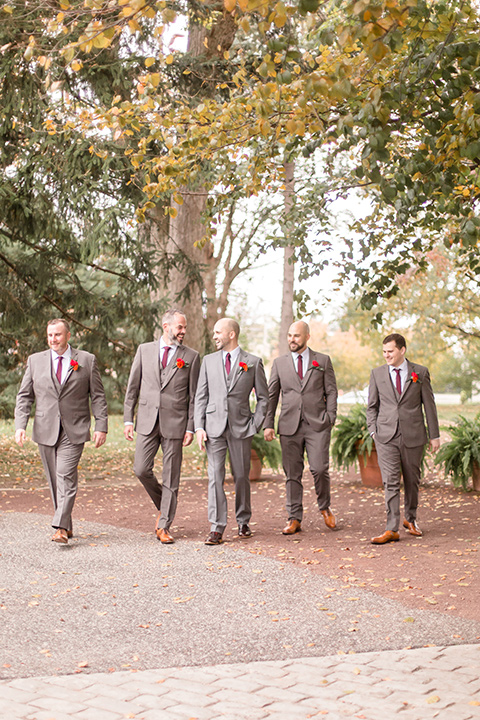 groom in a light brown suit with a red long tie and brown shoes, his groomsmen in a darker shade of brown suits with red ties