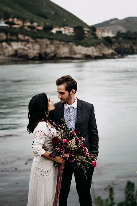 Avila-Beach-Styled-Shoot-bride-and-groom-by-ocean-looking-at-each-other-bride-in-a-bohemian-tea-length-dress-with-an-eylet-design-and-long-sleeves-the-groom-wore-a-navy-blue-suit-with-a-light-blue-shirt