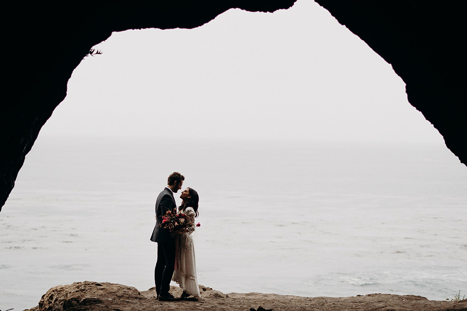 Avila-Beach-Styled-Shoot-bride-and-groom-in-cave-the-bride-wears-a-bohemian-gown-with-long-sleeves-and-a-high-neckline-this groom-is-in-a-navy-suit-with-light-blue-shirt