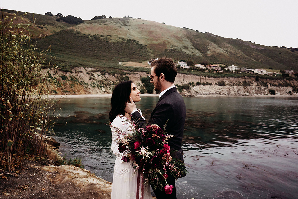 Avila-Beach-Styled-Shoot-bride-and-groom-looking-at-each-otherthe-bride-wears-a-bohemian-gown-with-long-sleeves-and-a-high-neckline-this groom-is-in-a-navy-suit-with-light-blue-shirt