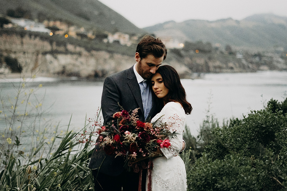 Avila-Beach-Styled-Shoot-bride-and-groom-looking-into-distance-the-bride-wears-a-bohemian-gown-with-long-sleeves-and-a-high-neckline-this groom-is-in-a-navy-suit-with-light-blue-shirt