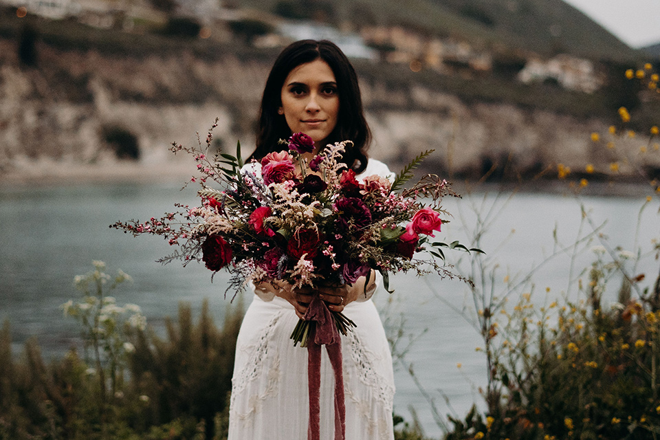 Avila-Beach-Styled-Shoot-bride-with-flowers-in-a-bohemian-gown-with-long-sleeves-and-a-high-neckline