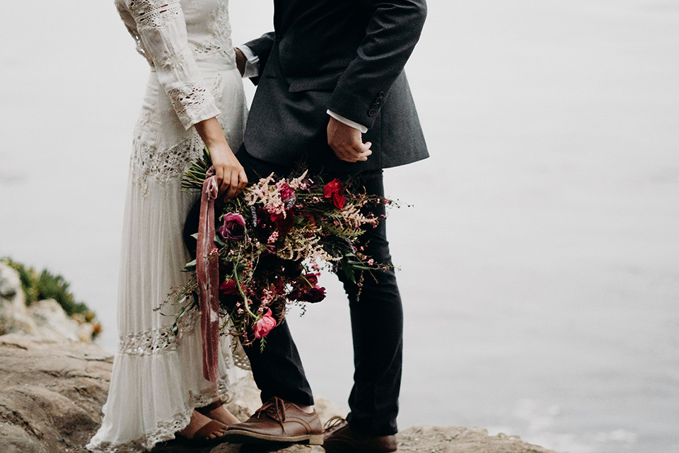 Avila-Beach-Styled-Shoot-close-up-of-bride-and-groom-attire-the-bride-wears-a-bohemian-gown-with-long-sleeves-and-a-high-neckline-this groom-is-in-a-navy-suit-with-light-blue-shirt