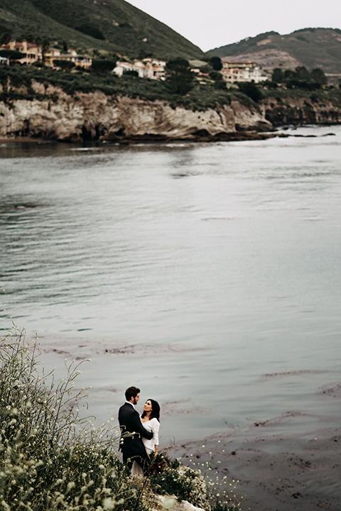 Avila-Beach-Styled-Shoot-far-away-shot-of-bride-and-groom-next-to-ocean-the-bride-in-a-bohemian-style-gown-with-an-eyelet-design-and-long-sleeves-the-groom-in-a-navy-blue-suit-with-a-light-blue-shirt