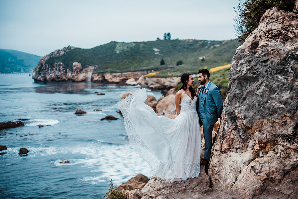 avila-beach-elopement-shoot-bide-and-groom-on-rockside-cliff-bride-in-a-flowing-white-gown-with-a-soft-tulle-overlay-the-groom-wore-a-light-blue-suit-with-a-navy-long-tie