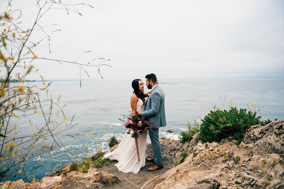 avila-beach-elopement-shoot-bride-and-groom-with-sweeping-views-behind-them-bride-in-a-flowing-white-gown-with-a-soft-tulle-overlay-the-groom-wore-a-light-blue-suit-with-a-navy-long-tie