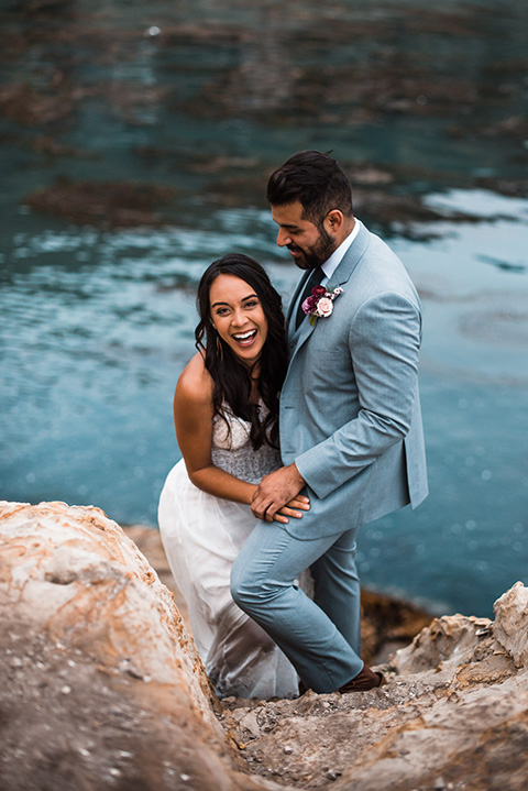 avila-beach-elopement-shoot-bride-laughing-groom-golding-her-steady-bride-in-a-soft-flowing-gown-with-a-strapless-neckline-and-the-groom-in-a-light-blue-suit-with-a-navy-long-tie