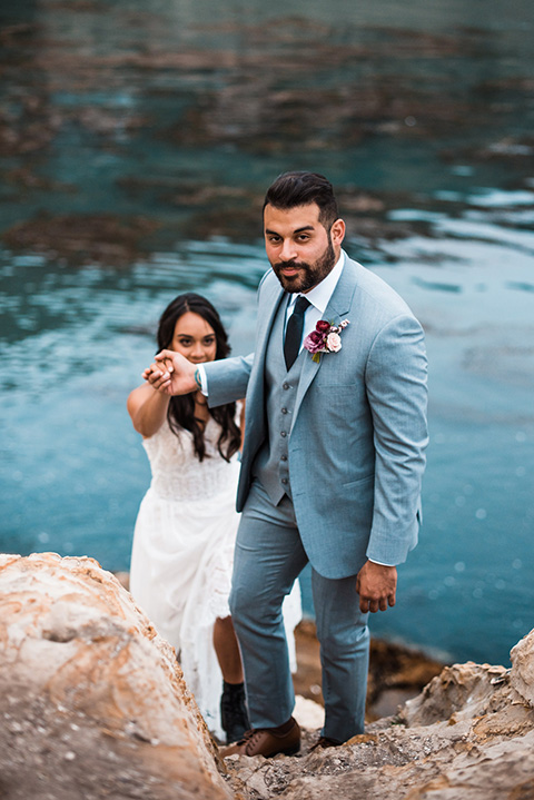 avila-beach-elopement-shoot-groom-helping-bride-up-groom-wearing-a-light-blue-suit-with-a-navy-long-tie-and-bride-in-a-strapless-tulle-flowing-gown