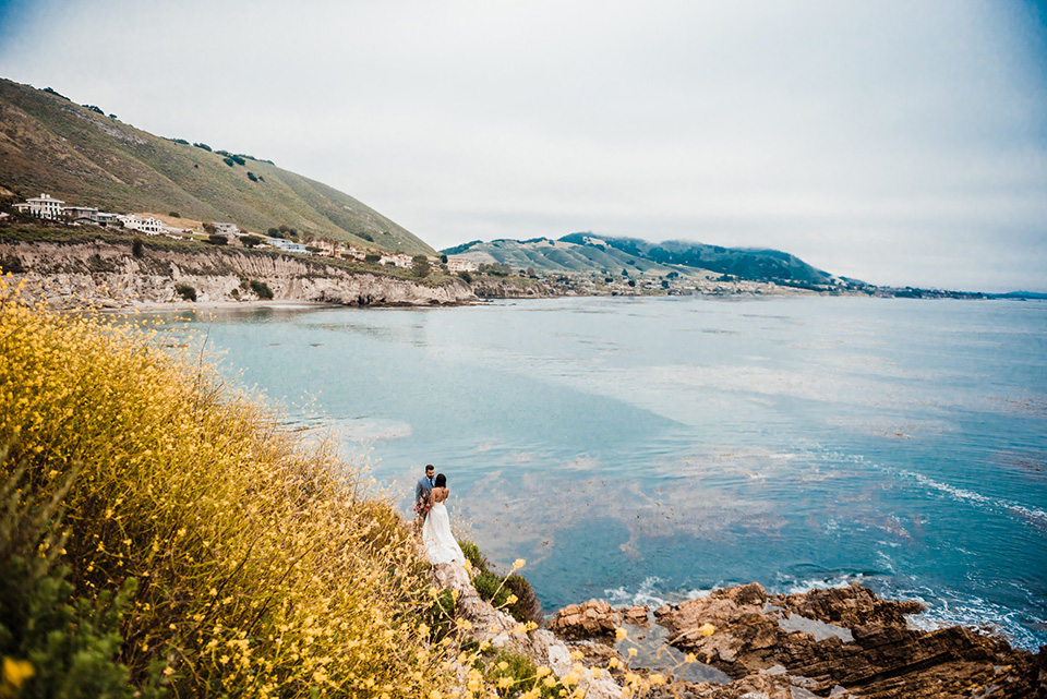 avila-beach-elopement-shoot-long-shot-of-bride-and-groom-bride-in-a-flowing-white-gown-with-a-soft-tulle-overlay-the-groom-wore-a-light-blue-suit-with-a-navy-long-tie