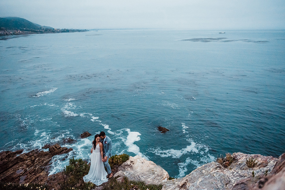 avila-beach-elopement-shoot-long-shot-of-ocean-and-couple-bride-in-a-flowing-white-gown-with-a-soft-tulle-overlay-the-groom-wore-a-light-blue-suit-with-a-navy-long-tie