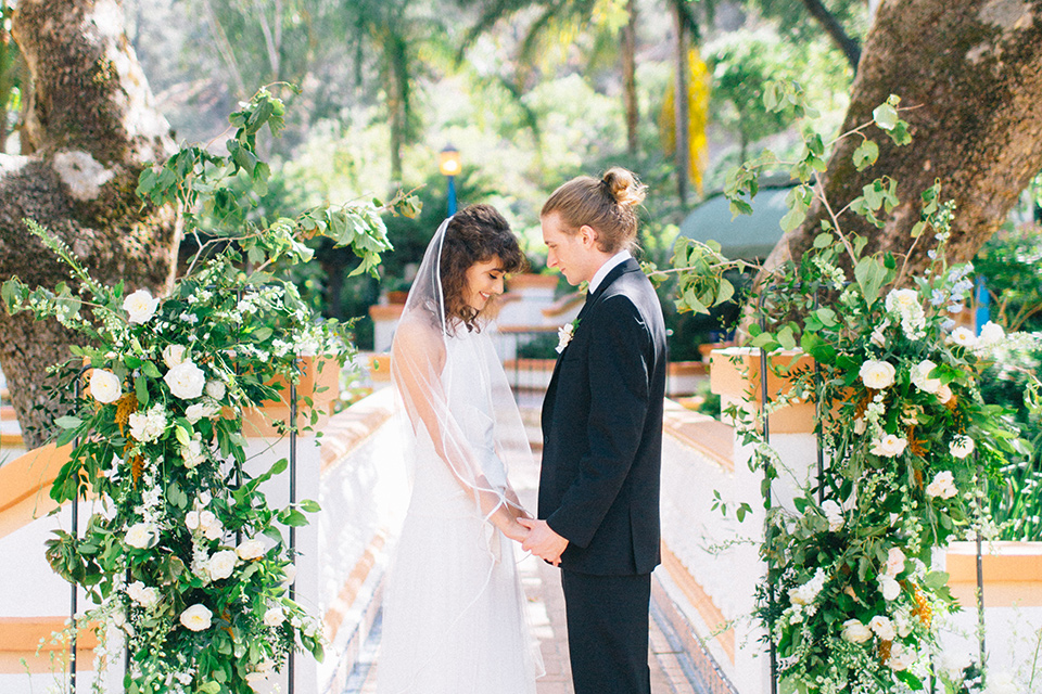 Rancho-las-lomas-blue-shoot-bride-and-groom-at-ceremony-looking-at-each-other-the-bride-wore-a-white-flowing-gown-with-a-halter-neckline-and-simple-mamkeup-the-groom-wore-a-simple-black-suit-with-a-black-long-tie