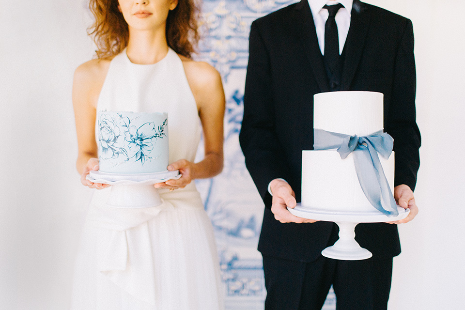 Rancho-las-lomas-blue-shoot-bride-and-groom-holing-cake-the-bride-wore-a-white-flowing-gown-with-a-halter-neckline-and-simple-mamkeup-the-groom-wore-a-simple-black-suit-with-a-black-long-tie