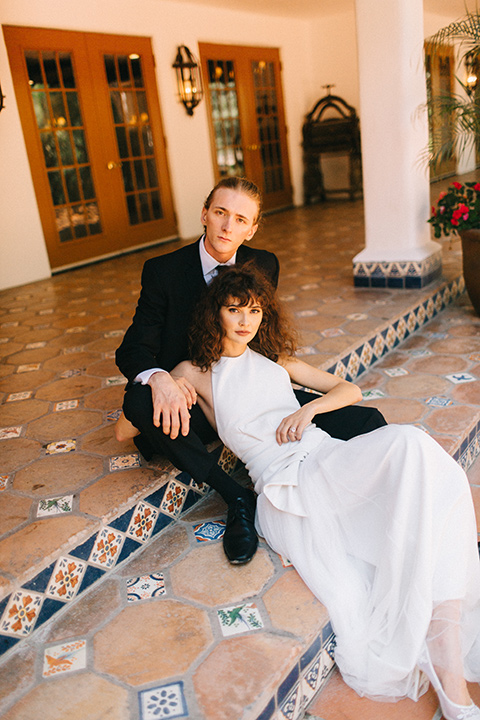 Rancho-las-lomas-blue-shoot-bride-and-groom-sitting-on-the-ground-the-bride-wore-a-flowing-white-gown-and-a-halter-neckline-and-the-groom-wore-a-black-suit-with-a-black-long-tie