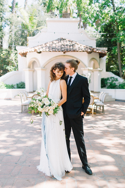 Rancho-las-lomas-blue-shoot-bride-and-groom-standing-smiling-the-bride-wore-a-white-dress-with-a-halter-neckline-and-black-notch-lapel-suit-and-black-long-tie