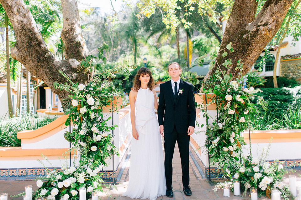 Rancho-las-lomas-blue-shoot-bride-and-groom-walking-away-from-ceremony-the-bride-wore-a-white-flowing-gown-with-a-halter-neckline-and-simple-mamkeup-the-groom-wore-a-simple-black-suit-with-a-black-long-tie