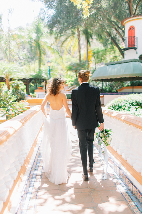 Rancho-las-lomas-blue-shoot-bride-and-groom-walking-away-the-bride-wore-a-flowing-white-gown-and-a-halter-neckline-and-the-groom-wore-a-black-suit-with-a-black-long-tie