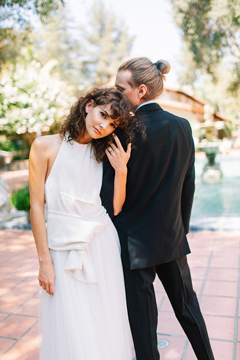 Rancho-las-lomas-blue-shoot-bride-facing-camera-groom-facing-away-from-camera-the-bride-wore-a-white-dress-with-a-halter-neckline-and-black-notch-lapel-suit-and-black-long-tie