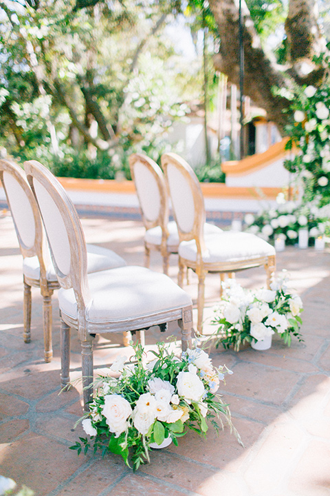 Rancho-las-lomas-blue-shoot-ceremony-chairs-in-a-light-wooden-stlye-with-white-linens-and-green-florals