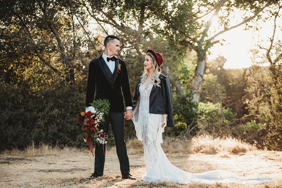 owl-creek-farms-bride-and-groom-touching-heads-bride-wearing-a-boho-lace-long-sleeved-gown-with-a-high-neckline-groom-wears-a-black-velvet-coat-with-grey-pants-and-a-black-bow-tie