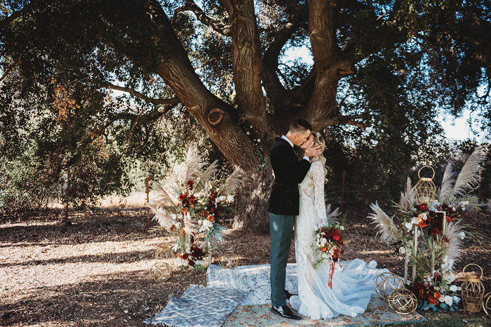 owl-creek-farms-bride-and-groom-kissing-under-tree-bride-wearing-a-boho-lace-long-sleeved-gown-with-a-high-neckline-groom-wears-a-black-velvet-coat-with-grey-pants-and-a-black-bow-tie