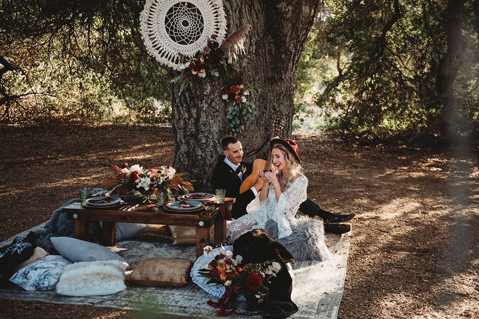 owl-creek-farms-bride-and-groom-sitting-with-instruments-bride-wearing-a-boho-lace-long-sleeved-gown-with-a-high-neckline-groom-wears-a-black-velvet-coat-with-grey-pants-and-a-black-bow-tie