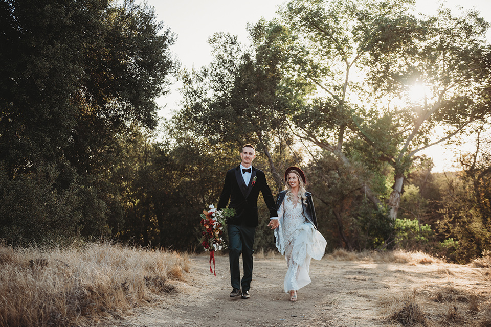 owl-creek-farms-bride-and-groom-walking-bride-wearing-a-boho-lace-long-sleeved-gown-with-a-high-neckline-groom-wears-a-black-velvet-coat-with-grey-pants-and-a-black-bow-tie
