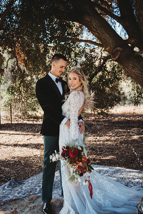 owl-creek-farms-bide-and-groom-touching-heads-owl-creek-farms-bide-and-groom-touching-heads-bride-wearing-a-boho-style-dress-with-long-sleeves-and-a-high-neckline-with-a-burgundy-wide-brimmed-hat-groom-wearing-a-velvet-tuxedo-with-grey-pants
