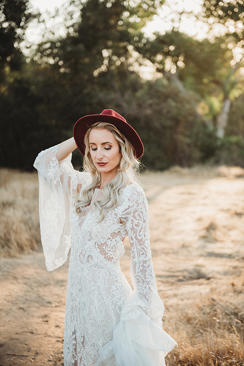 owl-creek-farms-bride-wearing-hat-bride-wearing-a-boho-style-dress-with-long-sleeves-and-a-high-neckline-with-a-burgundy-wide-brimmed-hat