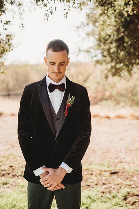 owl-creek-farms-groom-looking-down-wearing-a-velvet-tuxedo-with-grey-pants