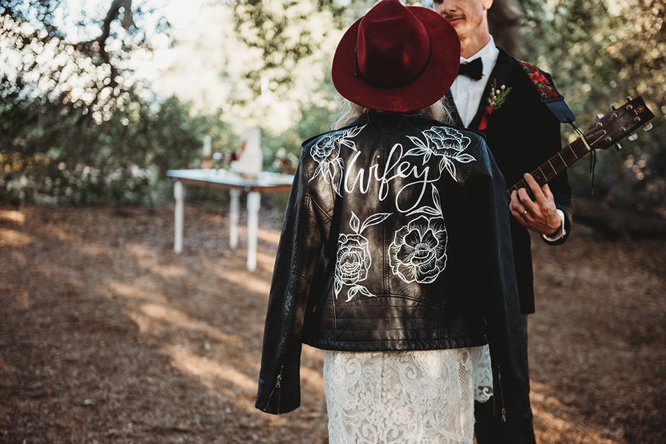 owl-creek-farms-leather-jacket-with-lettering-bride-wearing-a-boho-lace-long-sleeved-gown-with-a-high-neckline-and-leather-jacket-groom-wears-a-black-velvet-coat-with-grey-pants-and-a-black-bow-tie
