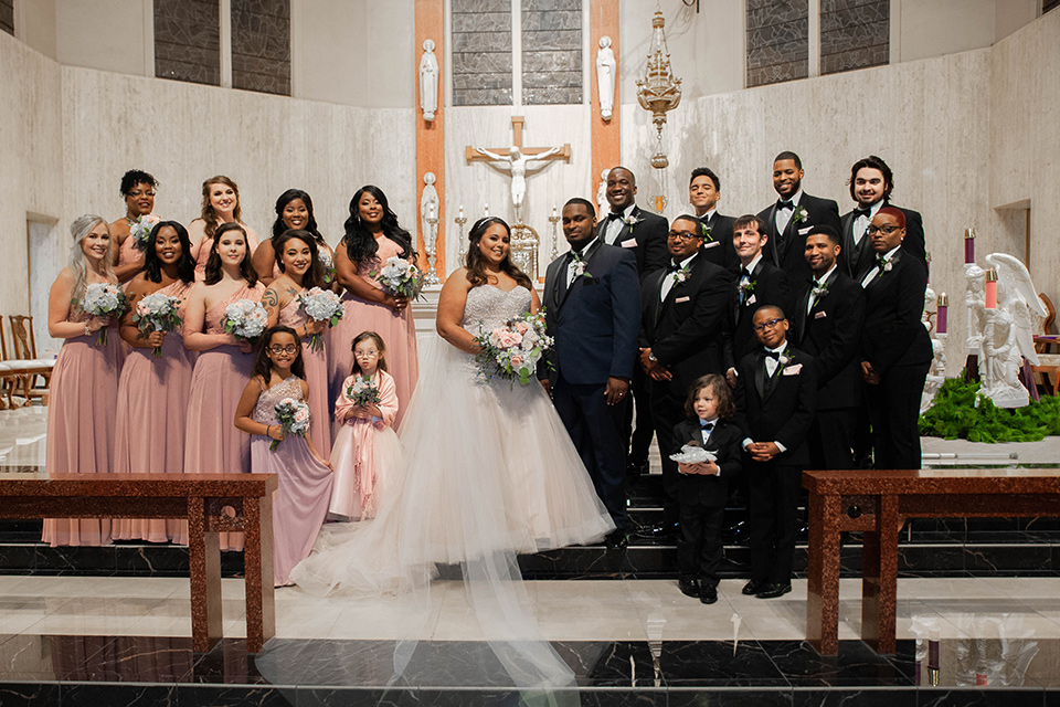 Fete-Venue-New-Orleans-Wedding-bridal-party-bridesmaids-in-pink-dresses-groomsmen-in-black-tuxedos-bride-in-a-tulle-strapless-ballgown-groom-in-a-navy-blue-tuxedo