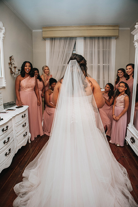 Fete-Venue-New-Orleans-Wedding-bride-looking-at-bridesmaids-bridesmaids-facing-camera-bridesmaids-in-pink-dresses-bride-in-a-strapless-ball-gown
