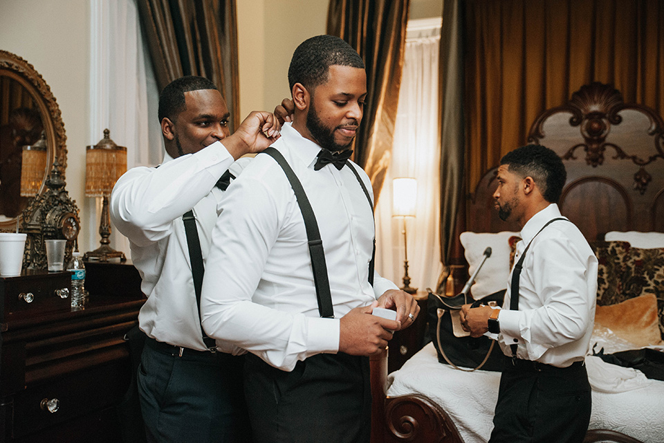 Fete-Venue-New-Orleans-Wedding-groom-getting-ready-groom-in-navy-tuxedo-with-a-shawl-lapel-and-groomsman-and-groomswoman-in-black-tuxedos