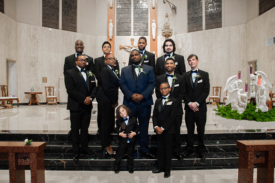 Fete-Venue-New-Orleans-Wedding-groomsmen-groom-in-navy-tuxedo-with-a-shawl-lapel-and-groomsman-and-groomswoman-in-black-tuxedos