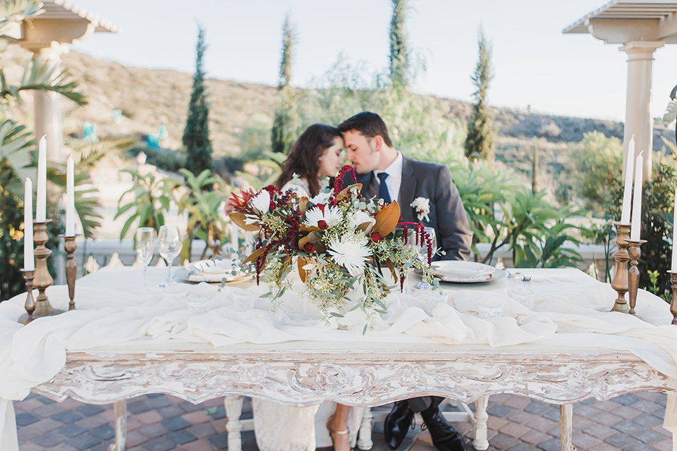 chateau-raquel-romantic-wedding-bride-and-groom-at-sweetheart-table-bride-wearing-a-lace-gown-groom-wearing-a-grey-suit