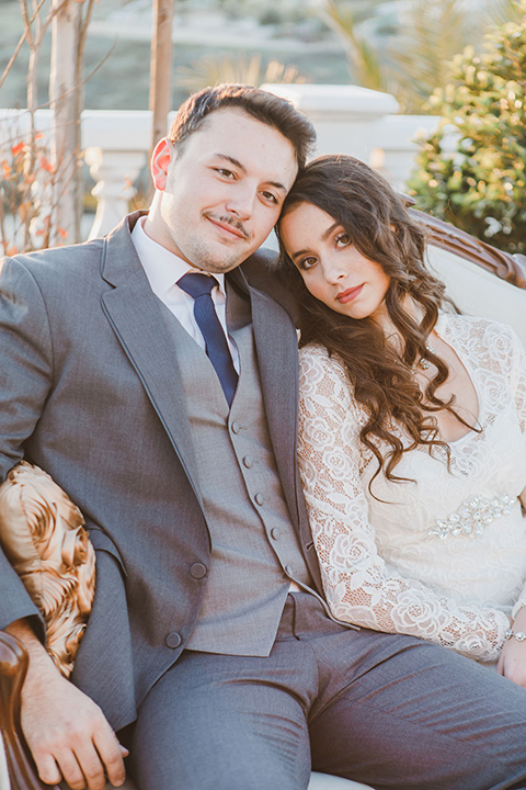 chateau-raquel-romantic-wedding-bride-and-groom-close-up-smiling-bride-wearing-a-lace-dress-with-sleeves-groom-in-a-dark-grey-suit-with-a-light-grey-vest