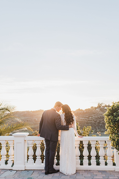 chateau-raquel-romantic-wedding-bride-and-groom-looking-out-to-distance-bride-wearing-a-lace-dress-with-sleeves-groom-in-a-dark-grey-suit-with-a-light-grey-vest