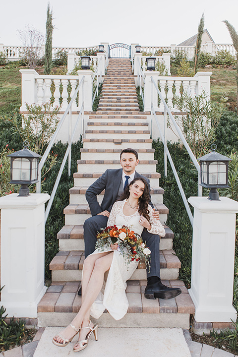 chateau-raquel-romantic-wedding-bride-and-groom-on-steps-bride-in-a-romantic-white-gown-with-sleeves-groom-in-a-dark-grey-suit