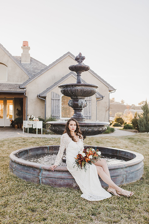 chateau-raquel-romantic-wedding-bride-by-fountain-wearing-a-white-lace-dress-with-sleeves