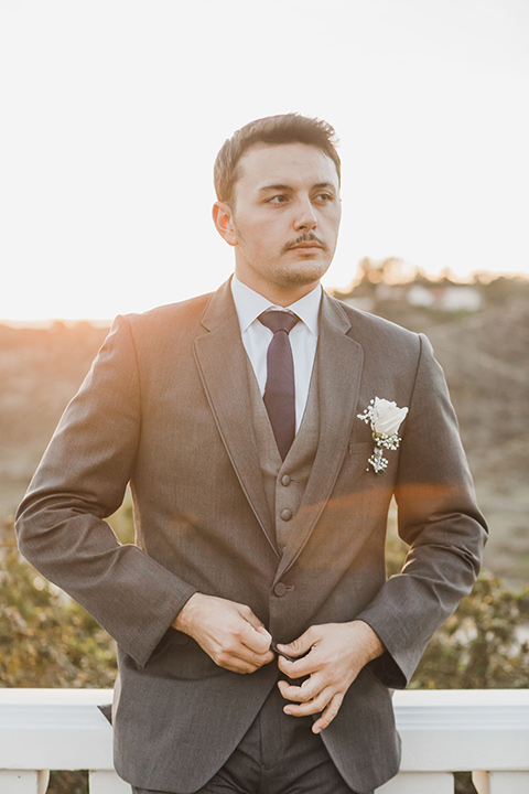 chateau-raquel-romantic-wedding-groom-model-buttoning-jacket-wearing-a-dark-grey-suit-jacket-and-pants-with-a-light-grey-vest
