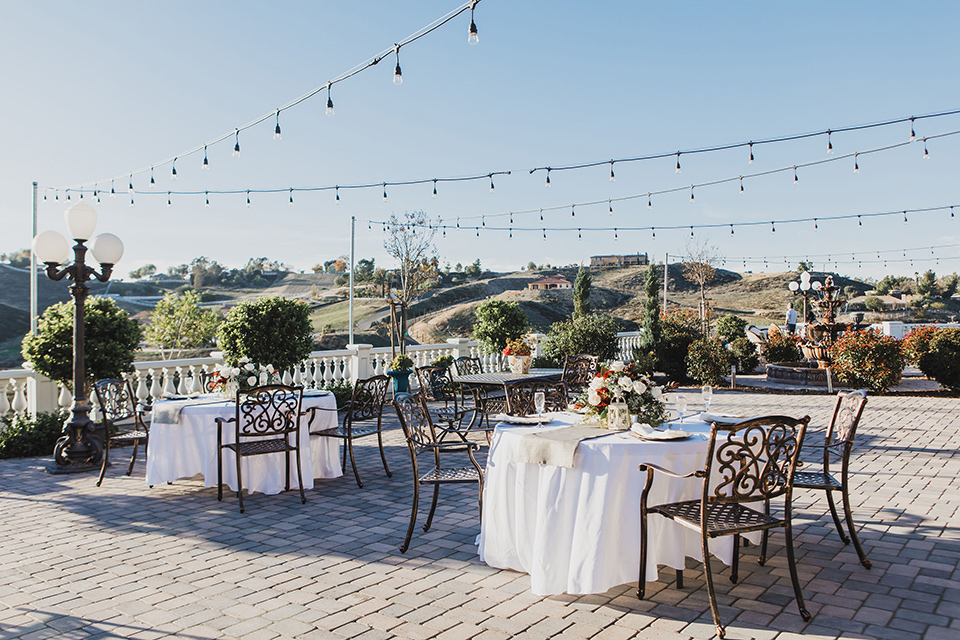 chateau-raquel-romantic-wedding-outdoor-reception-space-with-wooden-chairs-and-string-lights