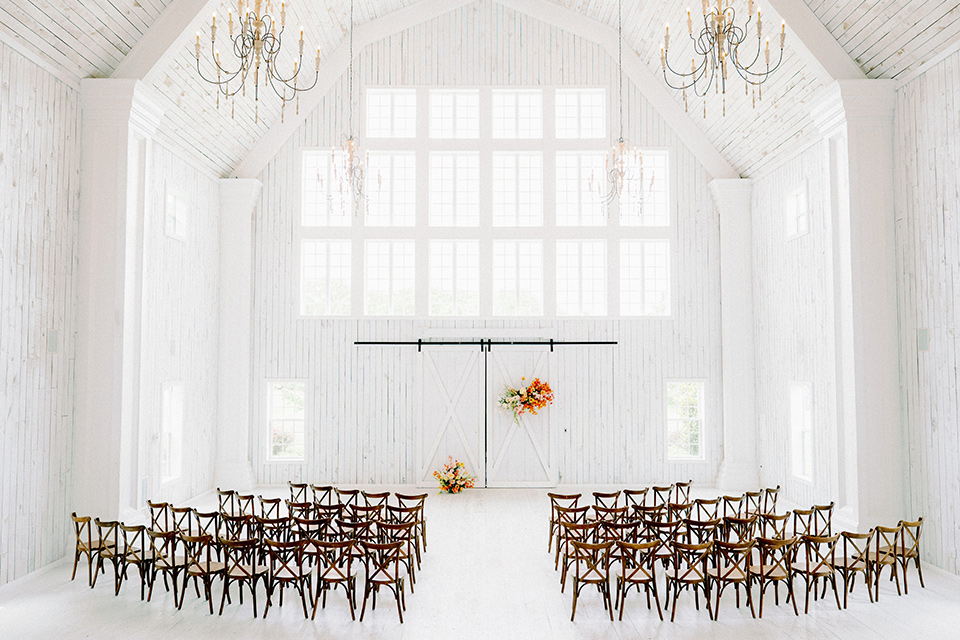 white barn interior with wooden chairs and golden florals