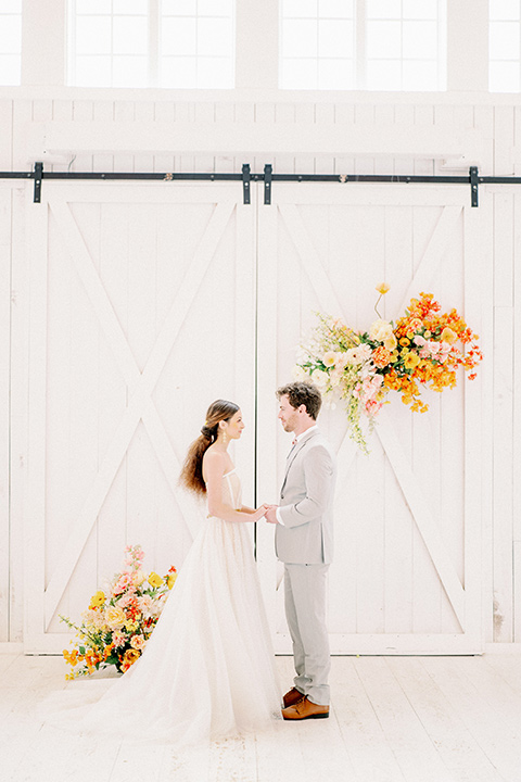 bride and groom at ceremony, bride in a full tulle ballgown with a strapless design and the groom in a light grey suit with pink bow tie