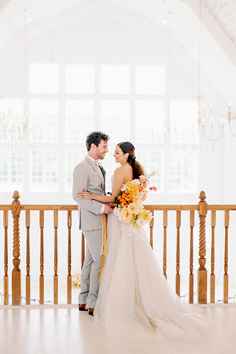 bride and groom close standing in loft, bride in a full tulle ballgown with a strapless design and the groom in a light grey suit with pink bow tie