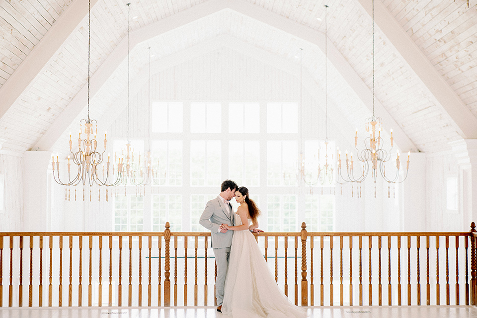 bride and groom standing on the loft, bride in a full tulle ballgown with a strapless design and the groom in a light grey suit with pink bow tie