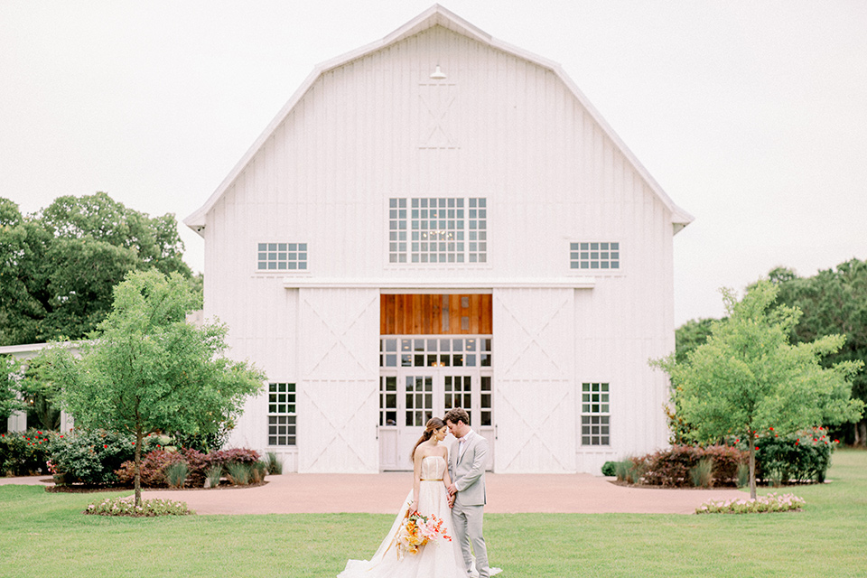 bride and groom outside the barn, bride in a full tulle ballgown with a strapless design and the groom in a light grey suit with pink bow tie