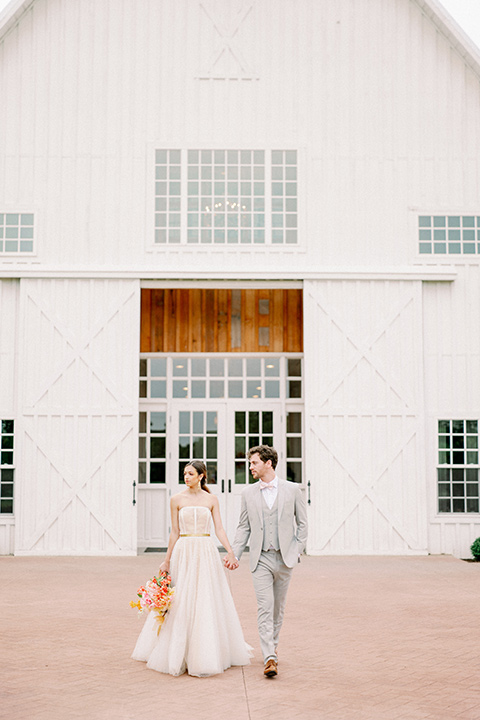 bride and groom walking outside venue, bride in a full tulle ballgown with a strapless design and the groom in a light grey suit with pink bow tie