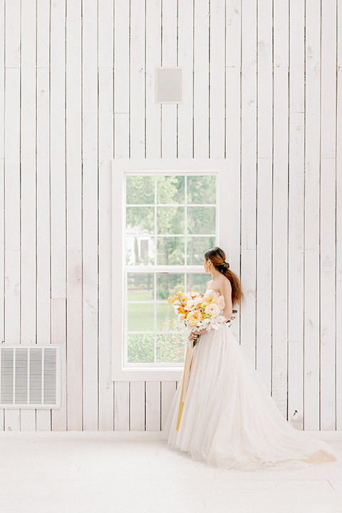 bride in a full tulle ballgown with a strapless design holding colorful golden toned flowers